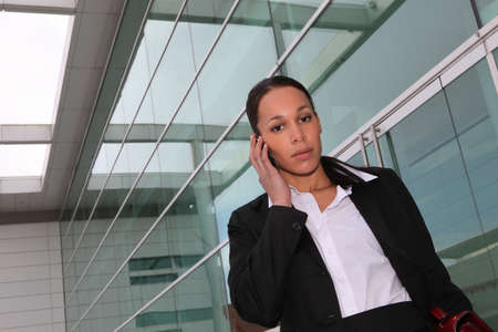 Businesswoman making phone call outside office Stock Photo - 13881515