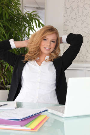 Blond woman stretching at her desk photo