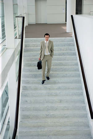 moving down: Man walking down stairs Stock Photo