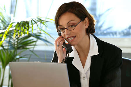 Woman on the phone at her desk Stock Photo - 13826829
