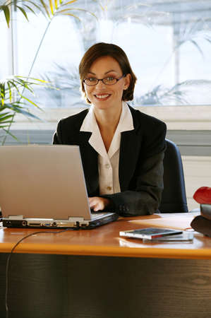 Businesswoman sitting at her desk Stock Photo - 13826506