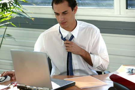 sweating: Stressed office worker loosening his tie Stock Photo