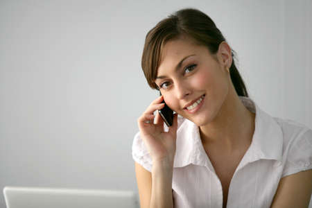 Brunette with laptop making telephone call photo