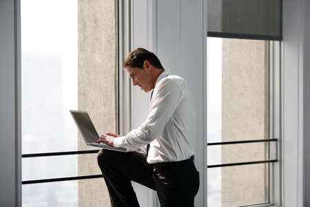 view of an elegant office: Businessman working on laptop near a window
