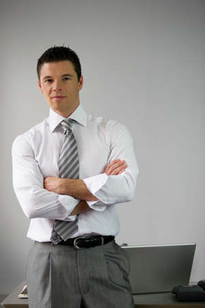 Serious businessman man by his desk arms folded Stock Photo - 13853546