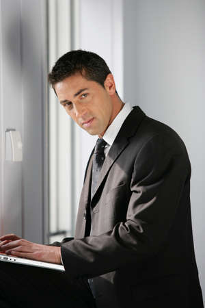 deceitful: Confident businessman using a laptop