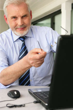60s adult: Man pointing to his laptop Stock Photo
