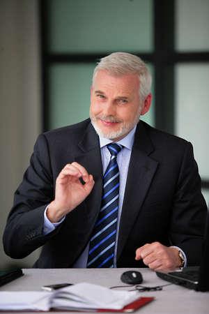 Senior businessman thinks everything is OK photo