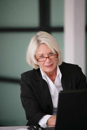 experienced: Senior businesswoman sending e-mails Stock Photo