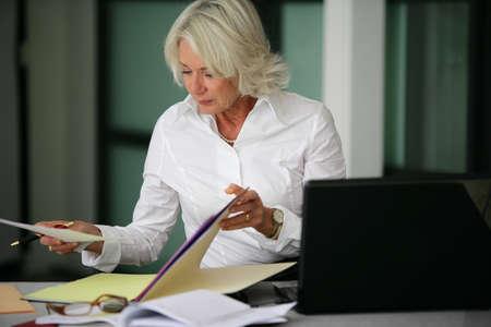 legal document: Una mujer mirando a través de algunos archivos