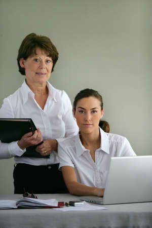 Female boss and young assistant photo
