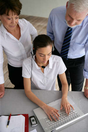 auspices: Business couple overseeing a woman talking through a headset Stock Photo