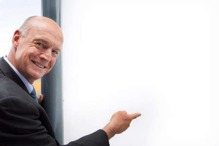Senior businessman pointing at copyspace photo
