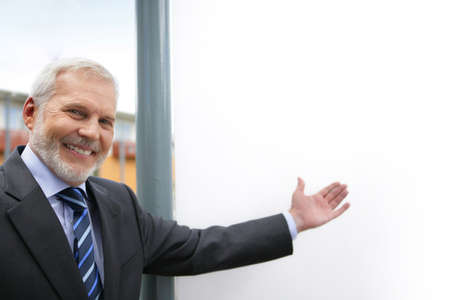 proffessional: Senior businessman drawing attention to blank poster