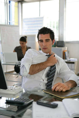 Man sat in office adjusting his tie photo