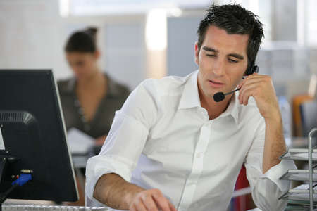 Young man telemarketer in call center photo