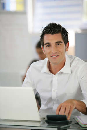 Man in a crisp white shirt using a laptop photo