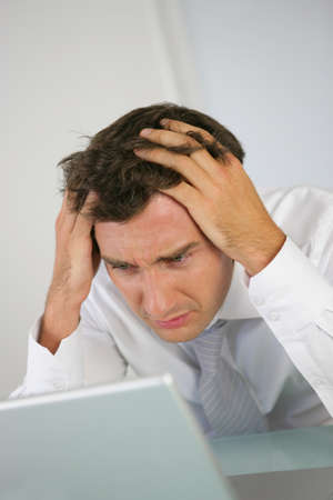 Businessman having a problem with his computer photo