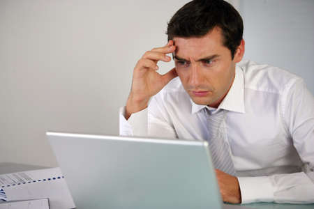 worried executive: Business man getting stressed at laptop