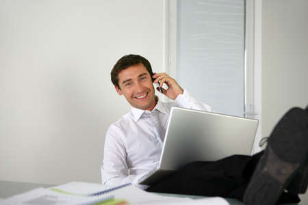 easy chair: Businessman sat with his feet on the desk