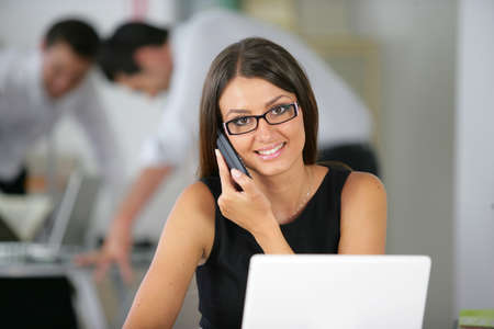 answering call: Friendly office worker with a phone and laptop Stock Photo