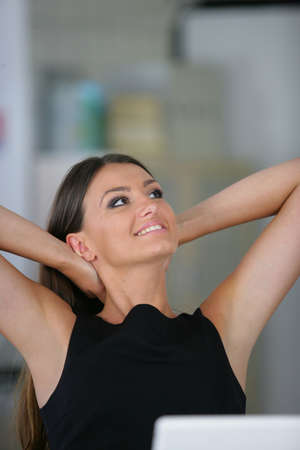 Woman sat at her desk stretching photo