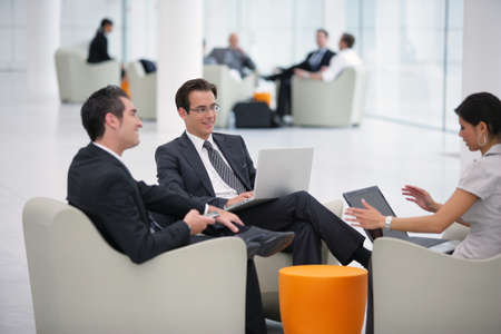 work area: Three businesspeople waiting at the airport