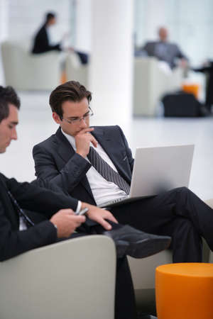 Businessmen waiting in airport lounge photo