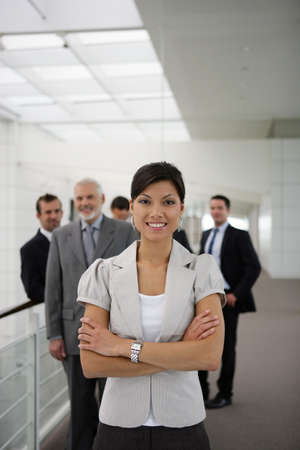 Smiling business woman standing cross-armed in workplace photo