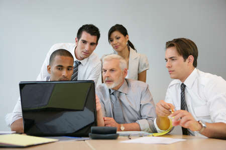 Business team sitting at a computer photo