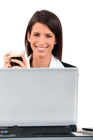 Smiling woman at laptop with coffee photo