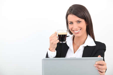 Woman drinking a coffee at her laptop photo