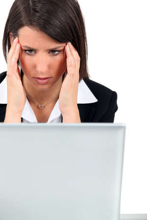 computer problem: Woman at work with a headache