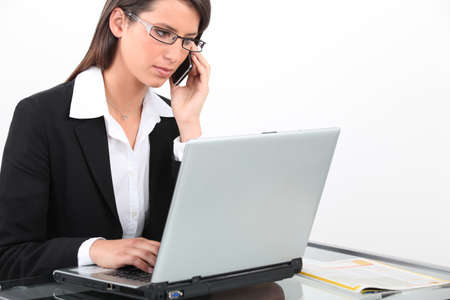 Brunette businesswoman using laptop and mobile telephone photo