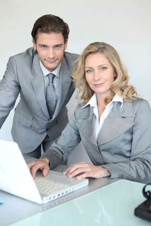 A businessman and a businesswoman working in front of a laptop and looking at us. Stock Photo - 13912377