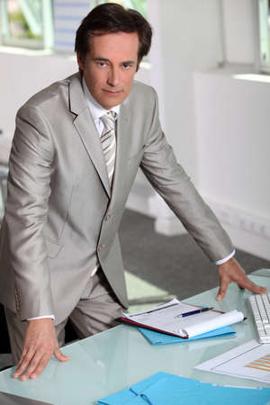 determined: Man in a silver-grey suit purposefully standing by his desk