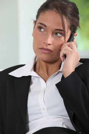 Young female executive using a mobile phone Stock Photo - 13897528