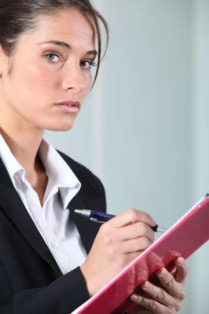Woman writing on clip-board photo