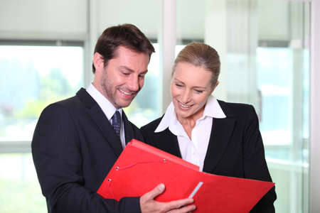 Businessman and woman looking at folder Stock Photo - 13880639