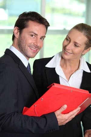 Businesswoman smiling at businessman Stock Photo - 13884582