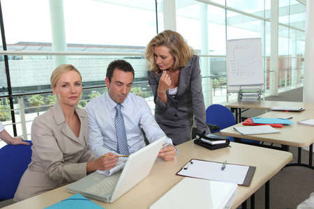 two women wearing suits and a man are working in a company photo