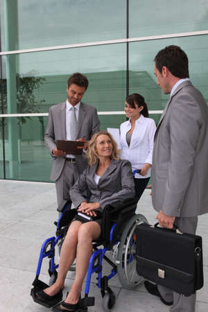 Businesswoman in a wheelchair with colleagues outside an office building photo