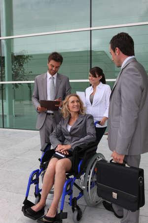persona en silla de ruedas: Empresaria en una silla de ruedas con colegas fuera de un edificio de oficinas
