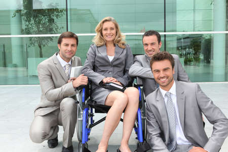 Female executive in wheelchair with colleagues outside office building photo