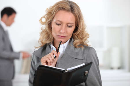 Businesswoman looking at diary photo