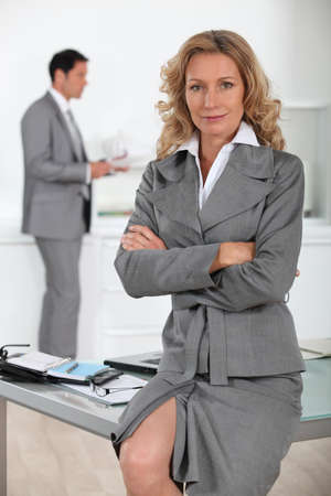 Businesswoman sitting on desk with arms folded photo