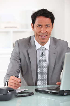 Businessman sitting at his desk with a laptop computer Stock Photo - 13882044