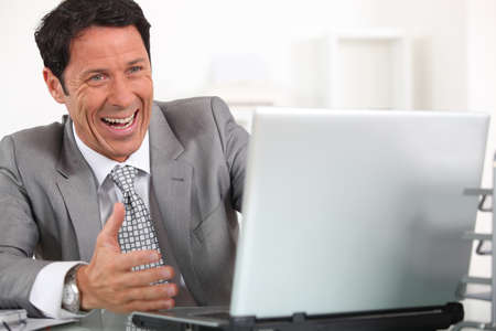 hilarity: Man laughing hysterically at his laptop computer
