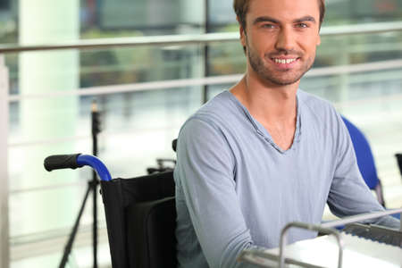 wheelchair access: Wheelchair user working at a desk Stock Photo