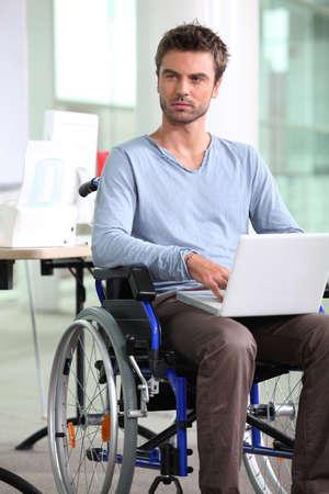 empleado en silla de ruedas con ordenador port�til Foto de archivo - 13884827